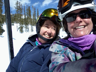 Two ladies on a chair lift.