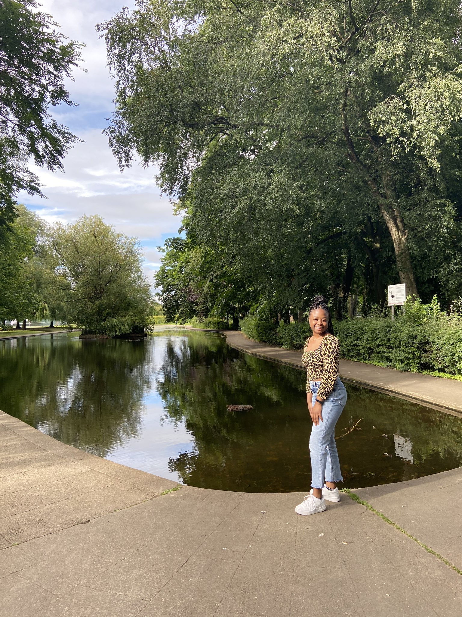 A picture of smiling at the camera standing next to a lake surrounded by greenery wearing blue jeans, white trainers and a leopard print top