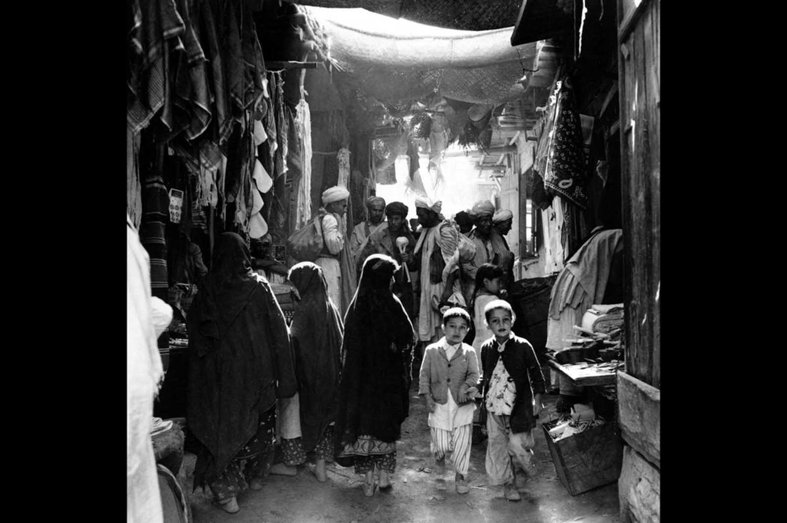 Afghan boys, men, and women, some in bare feet, shop at a marketplace in Kabul, Afghanistan, in May of 1964.