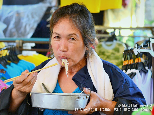 Matt Hahnewald; Facing the World; Asia; people; noodles; chop sticks; street portrait; closeup; eating; slurping; food; travel; travel destination; Southeast Asia; Northern Thailand; Chiang Dao; Tuesday market; market woman; Thai woman; eye contact; lunch break; Nikon DSLR D3100; 50 mm prime lens