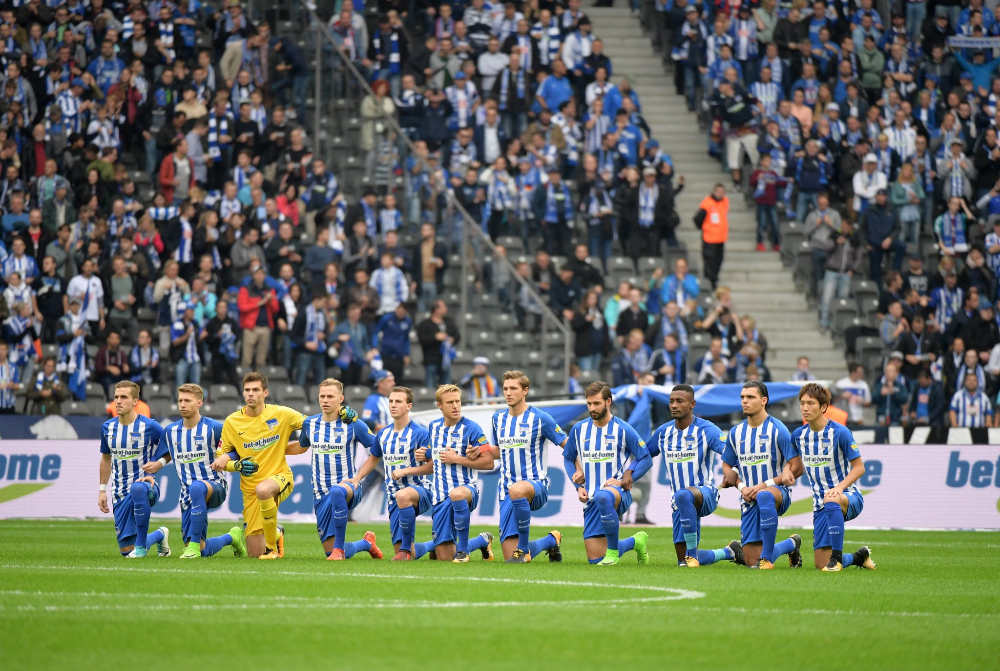 Hertha Berlin players take a knee before their Bundesliga match against Schalke