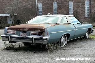 Four flat tires and weeds growing through parking lot cracks around car.