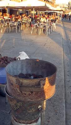 Assador de castanhas e mesinhas com pessoas ao fundo