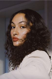 Profile picture of Anja Saleh, a light-skinned woman of colour. She sits sideways to the camera and turns her head to look directly in the lense. She has a serious expression on her face.