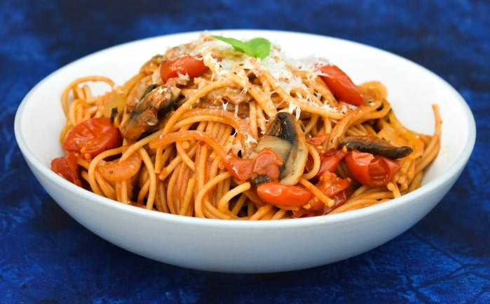 a bowl of spaghetti with mushroom and cherry tomato sauce