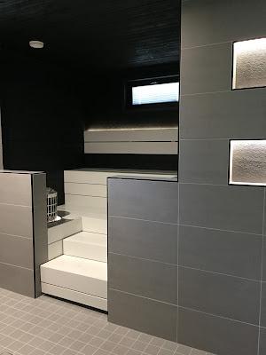 Siparila, mustavalkoinen sauna, valkoiset lauteet, musta saunapaneeli, harmaa pesuhuone, harmaat laatat