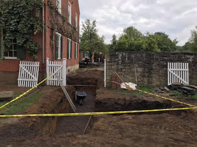 Multi-story brick building in upper right corner of photo. In forefront, several trenches have been dug for installation of pipes. Yellow caution tape blocks the trenches.