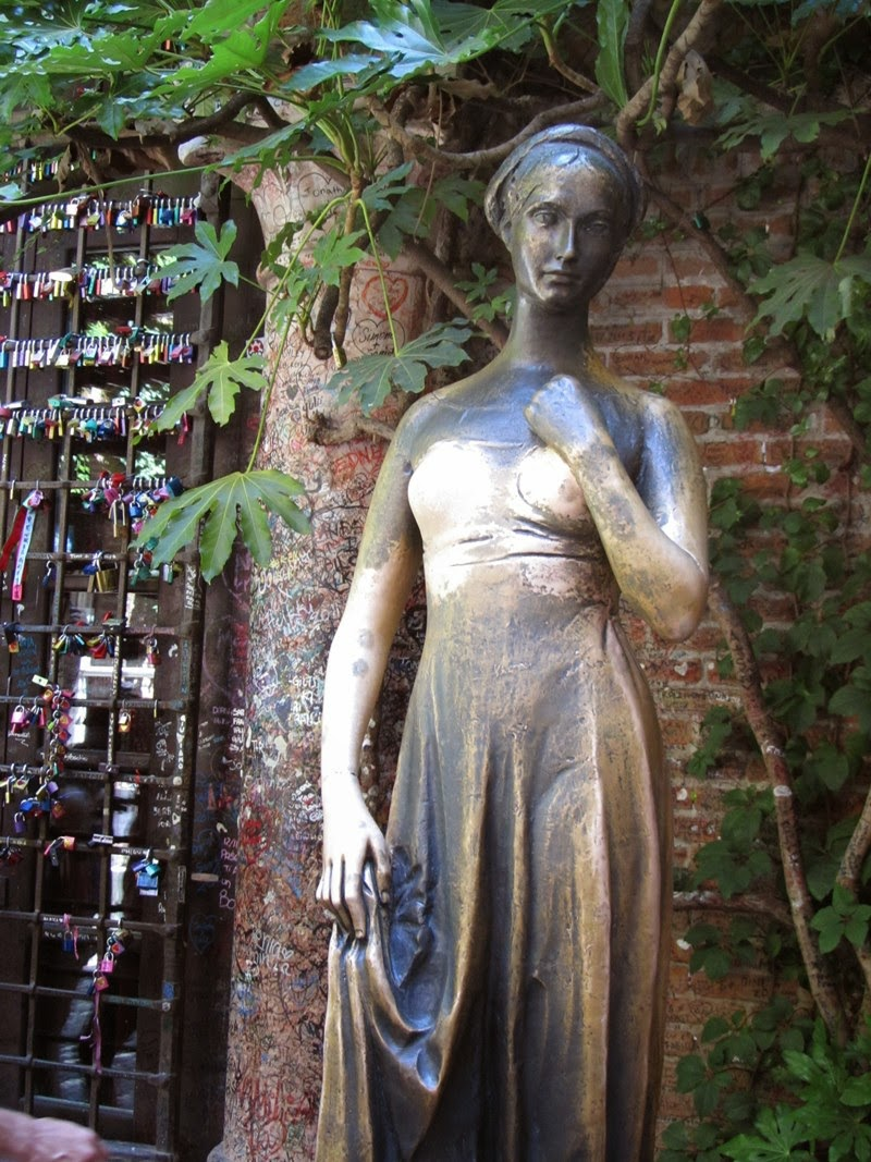 Italy - Veneto - Verona - Statue of Juliet outside Juliet's House — Tour of Italian lakes region of Italy including Garda, Como, Lugano, Maggiore and Orta. There is some truth behind the legend of Juliet and Romeo's story - the two families, Montecchi and Capuleti in Italian, were involved in a struggle for power in Italy during the period of the Scala lords. The house in Verona known as Juliet's house was owned by the family dell Capello. The house dates from the 13th century and the family coat of arms can still be seen on the wall. A slight problem is the balcony itself, which overlooks the courtyard – it was added in the 20th century.