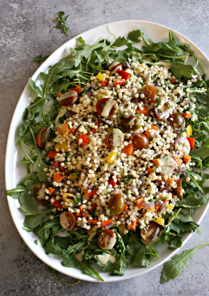 Recipe for a couscous salad loaded with vegetables and topped with tahini dressing.