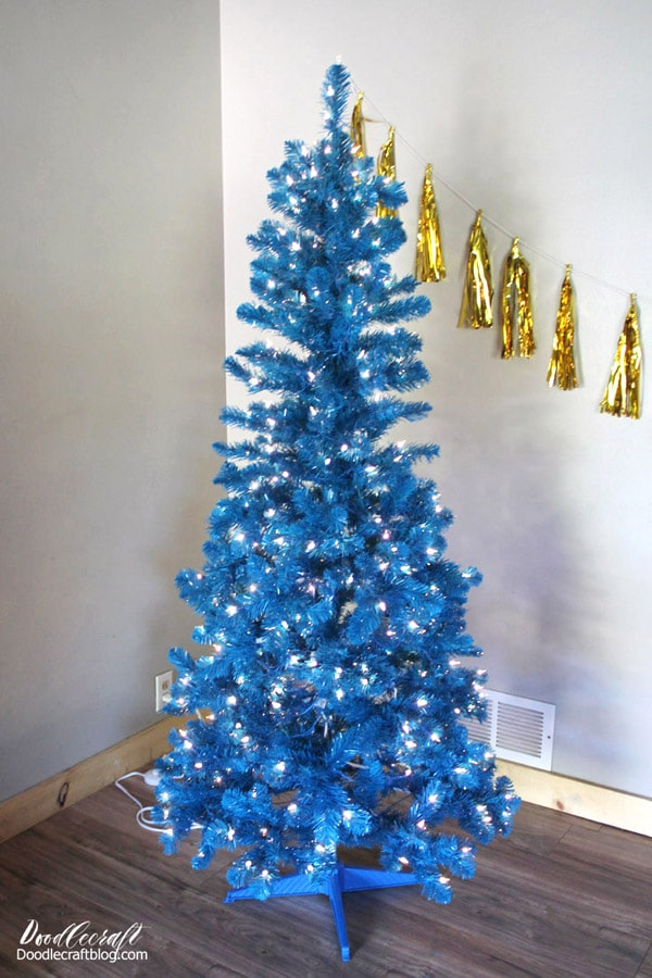 Blue slim pencil Christmas tree decorated with white lights from treetopia