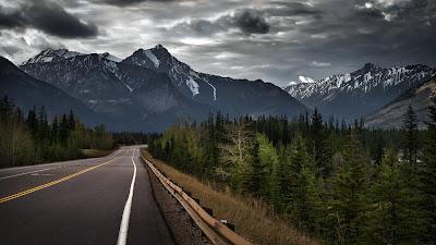 Impresionante paisaje con bosque, carretera y montañas de fondo con cielo nublado
