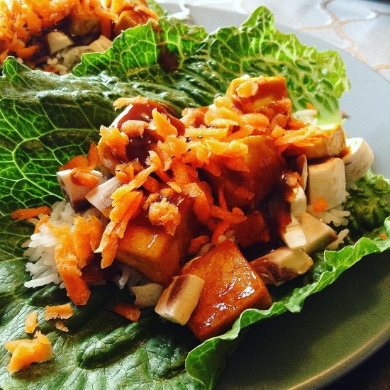 Square photo of a lettuce wrap filled with rice, tofu, mushrooms, grated carrot, and brown sauce.