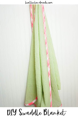 green swaddle blanket with pink trim