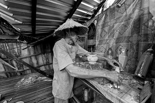 Ông Trần Văn Thum dọn lại bàn thờ tổ tiên trước khi tìm cách dựng lại ngôi nhà đã bị hư hại rất nhiều.