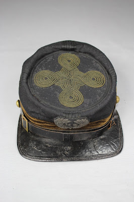 Forage cap conservation and mounting for stabilization using brim constructed of Vivak and covered with cotton fabric. Military artifacts are conserved, preserved and repaired at at Spicer Art Conservation, serving institutions and private owners
