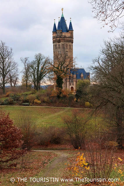 Landscaped park with a stone tower in the background under a grey winter sky.