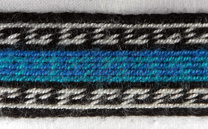 A black, white and blue/ green tablet woven band