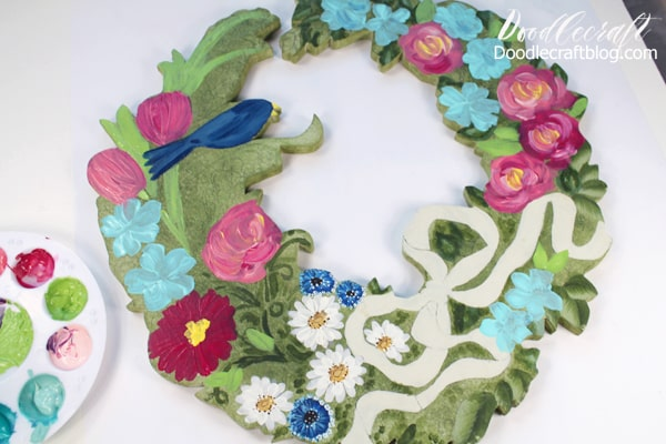 Painting flowers on a wooden cut out wreath.