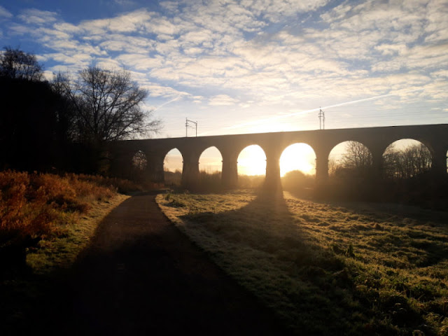 The morning sun is shining through the brick arches of a railway bridge.  The path and grass to the side of it is covered with frost