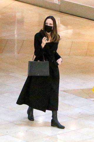 Angelina Jolie in all-black shopping outfit with leather bag, knee-high boots and face mask - News