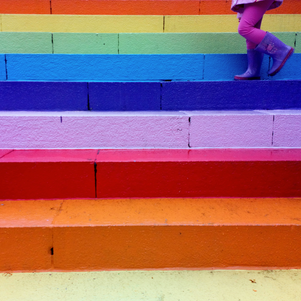 Kid's feet on steps painted rainbow colours