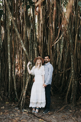 couple standing in front of trees smiling