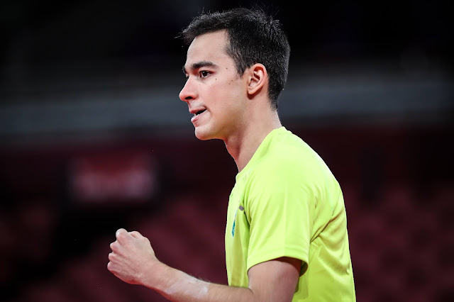 Hugo Calderano, de lado, comemorando um ponto. O brasileiro veste uma camisa amarela do Time Brasil