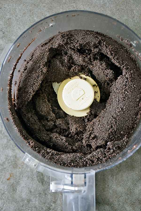 Crushed oreo crust in food processor ready to be spread in springform pan for Raspberry White Chocolate Cheesecake