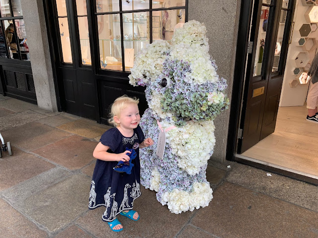 Child pretending to be a rabbit and posing next to a large rabbit covered in fake flowers outside a covent garden shop
