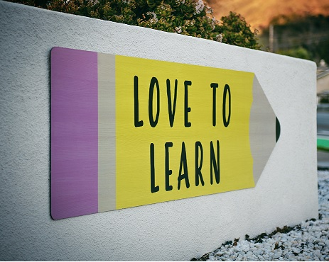 A sign that reads 'love to learn' on a large pencil shape on a concrete wall