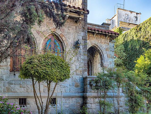Frente de una casa estilo colonial protegida por plantas.