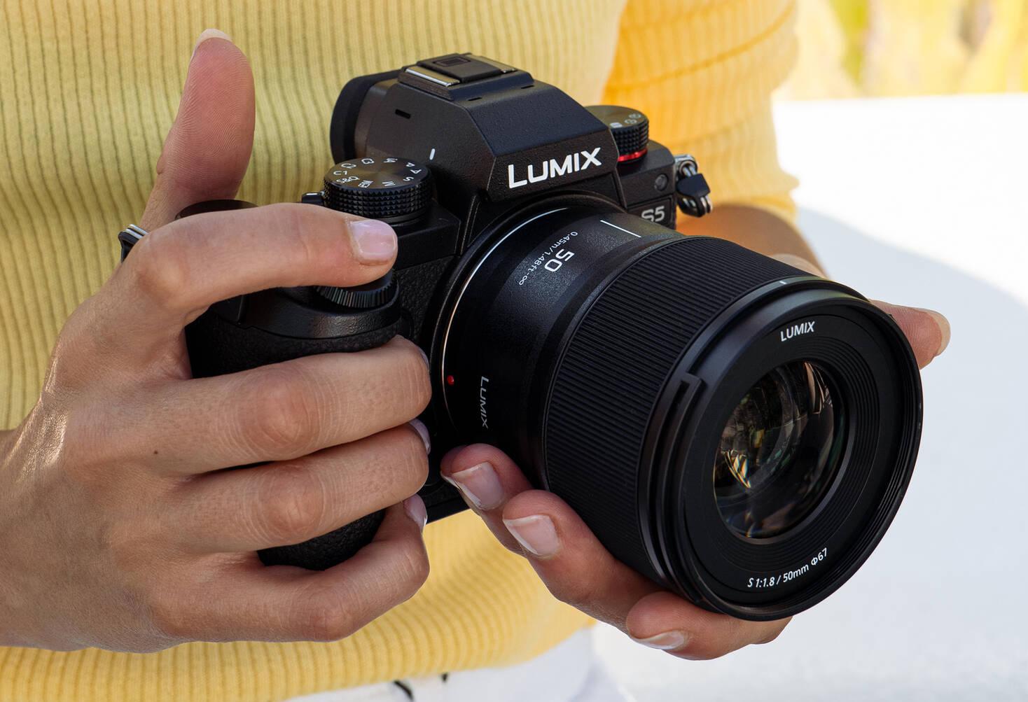 Камера Panasonic Lumix S5 с объективом Lumix S 50mm f/1.8 в руках фотографа