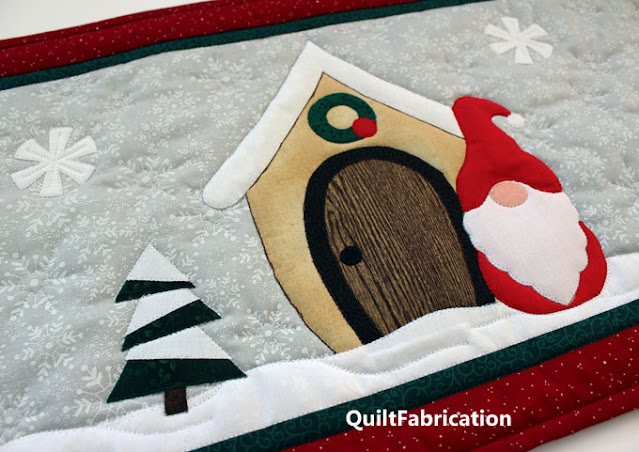red dressed gnome, snow covered beige house, pine tree