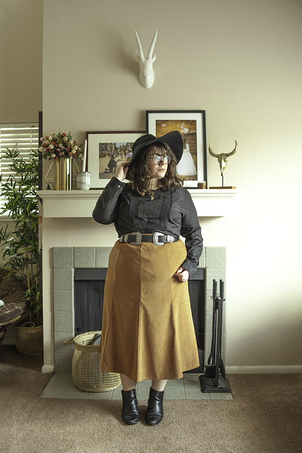 An outfit consisting of a black wide brim hat, a black peasant style long sleeve blouse with a key hole cutout in the front, camel brown a-line midi skirt with black Chelsea boots.