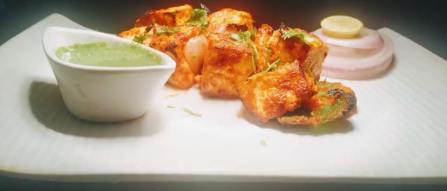 Paneer Tikka serve with slice onions, lemon wedges and green chutney for Paneer Tikka recipe