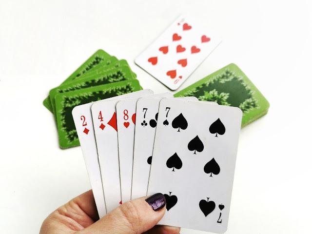 kobieca ręka trzymająca pięć kart, w tle widać stos kart i zakryte karty przeciwnika