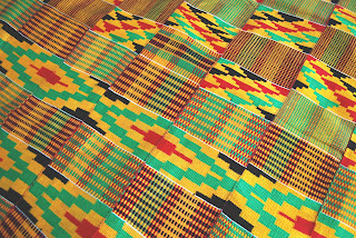 Yellow, red, green, and black kente cloth pattern