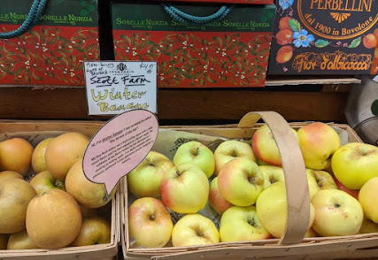 """A basket of yellow, extremely ribbed apples with a label that reads """"Winter Banana."""""""