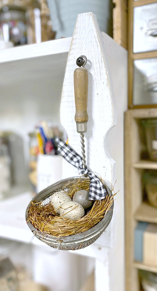 Spring decoration using a vintage Kitchen strainer and a birds nest