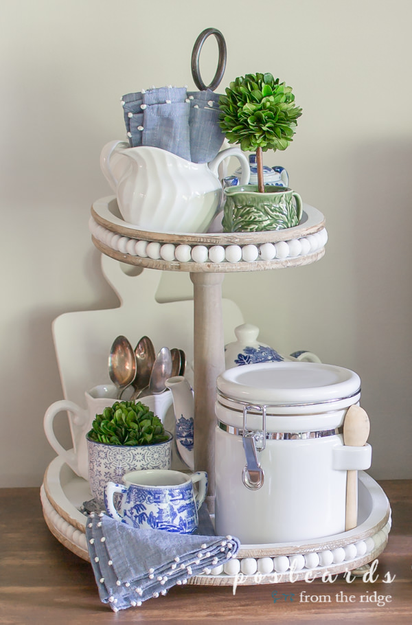 blue and white vintage and thrifted items in a wooden tiered tray