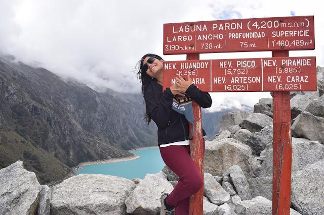 mulher abraçando uma placa escrita laguna paron