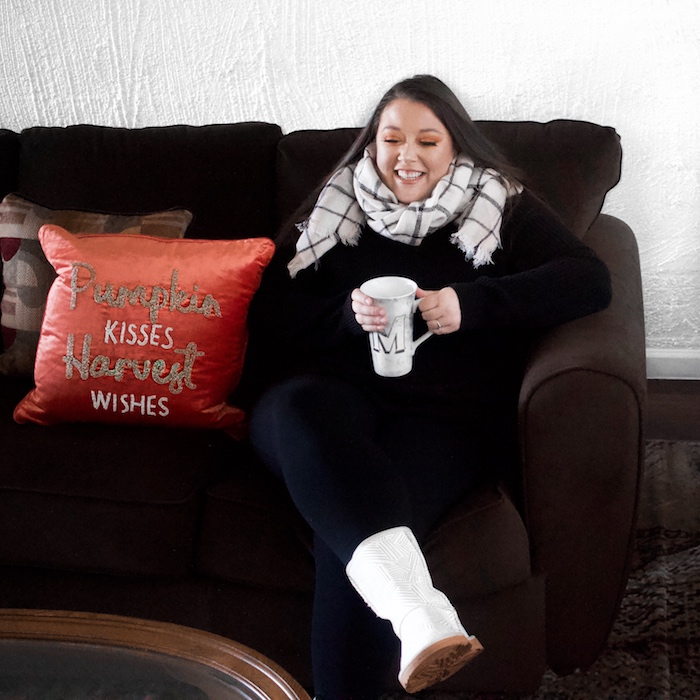 "Woman on the couch holding a large coffee mug next to a fall pillow ""pumpkin kisses harvest wishes"""