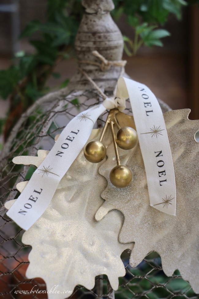 give a gold berry leaves ornament French Country style with a Noel ribbon
