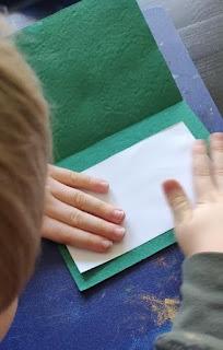 Pienet kädet liimaavat kartonkeja yhteen kortille