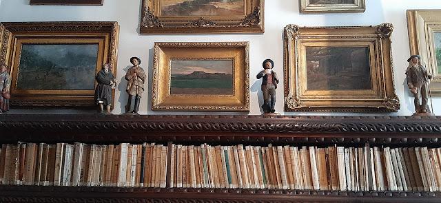 Estante com livros e esculturas e quadros
