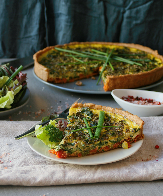 A slice of vegetable and tomato pesto tart.
