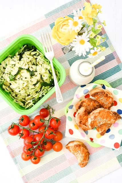 Plant-based picnic spread including pasta salad, cherry tomatoes and puff pastry parcels