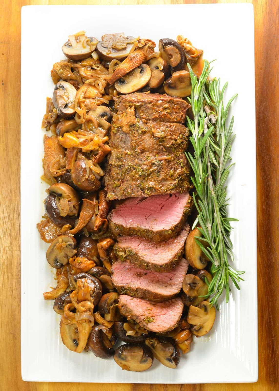 Tender Beef Tenderloin Roast with a delicious herb butter crust and easy to make sautéed mixed mushrooms is an elegant yet easy to make recipe that melts in your mouth. Recipe from Serena Bakes Simply From Scratch.