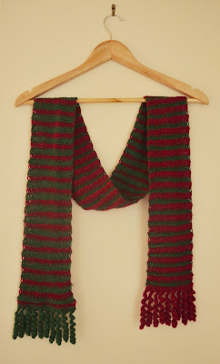 The scarf is draped loosely over a triangular wooden coathanger as if it were draped over someone's shoulders. Each end of the scarf hangs on either side of the coathanger, the green main colour side facing on the left, the red main colour side facing on the right.