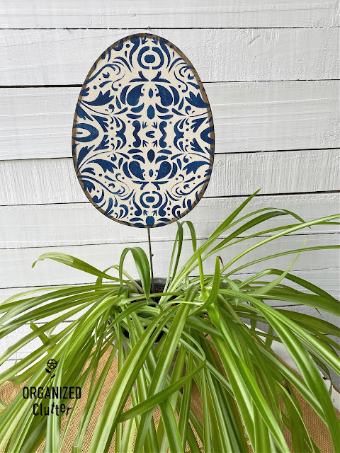 Photo of a painted & stenciled egg shape on a stake
